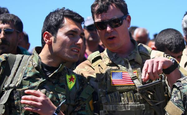 President Trump's plan for the Turkish-Syrian border contradicts recommendations from top officials in the Pentagon and the State Department. In this 2017 photo, a U.S. officer from the coalition against ISIS speaks with a fighter from the Kurdish People'