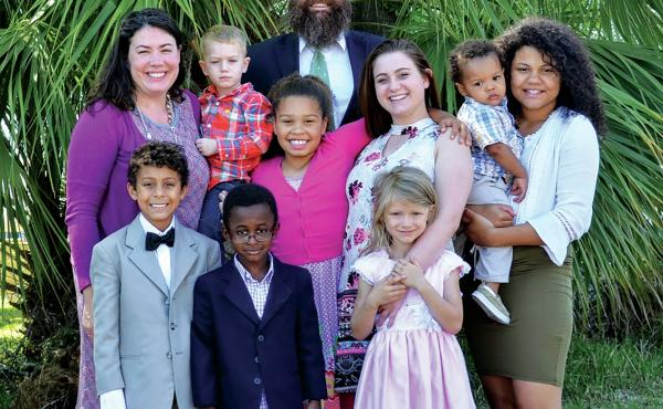 """""""We would not be able to foster without Medicaid,"""" says Sherri Croom of Tallahassee, Fla. Croom and her husband, Thomas, have fostered 27 children in the past decade. They're pictured here with four adopted children, two 18-year-old former foster daughter"""