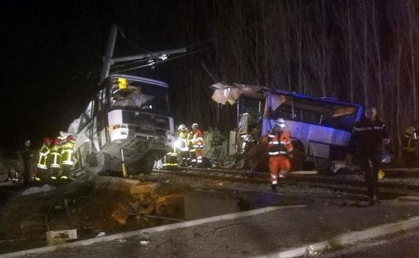 Rescue workers help after a fatal collision between a school bus and a regional train in the village of Millas in southern France on Thursday.