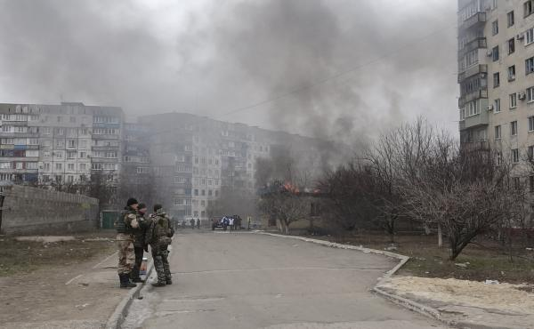 Ukrainian servicemen stand guard on a street near a burning building after a shelling by pro-Russian rebels of a residential sector in Mariupol, eastern Ukraine, last month.