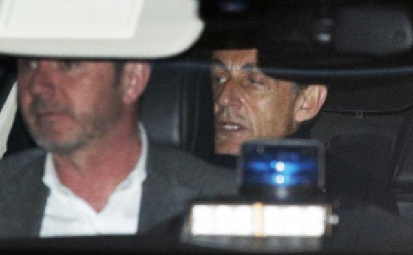 Former French President Nicolas Sarkozy, right, leaves the police station where he was held, in Nanterre, outside Paris, on Wednesday.
