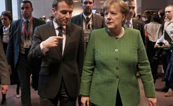 French President Emmanuel Macron speaks with German Chancellor Angela Merkel in Brussels last month.