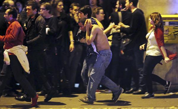An injured man holds his head as people gather near the Bataclan. At least three sites were attacked — a restaurant, the Bataclan and a site near a major stadium.