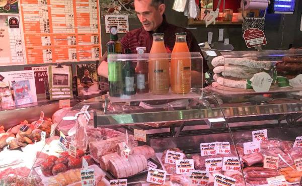 Didier Tass, behind the counter of his butcher shop, says he purchases meat from small farmers who raise cows and butcher them humanely and in small quantities.
