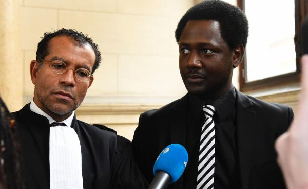 Souleymane Sylla (right) with his lawyer in Paris on Tuesday during the trial of the four British men accused of racist violence towards him in February 2015.