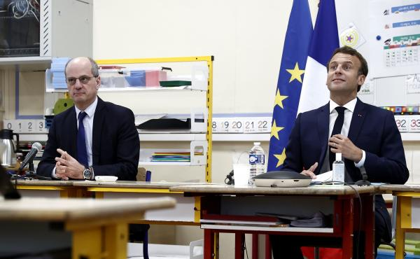 French Education Minister Jean-Michel Blanquer (left) and French President Emmanuel Macron participate in a video conference with mayors and directors of schools at the Pierre Ronsard elementary school in Poissy, west of Paris, on Tuesday.