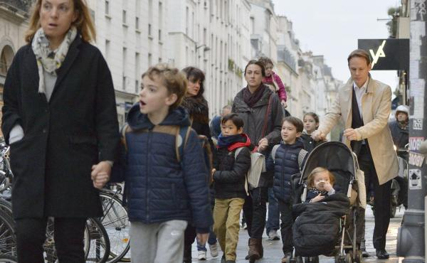 Parents walk their children to school on Monday near one of the venues attacked in Paris.