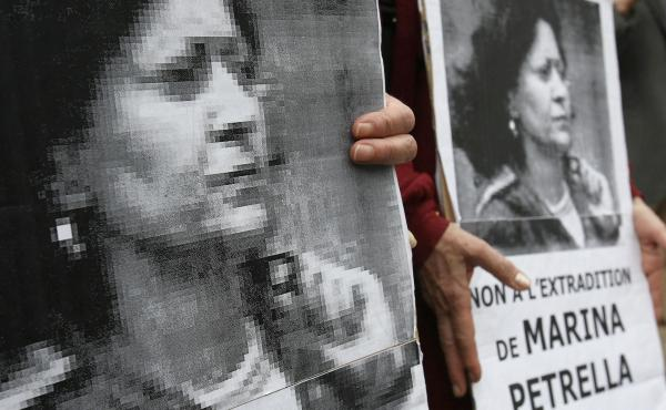 In 2008, people hold portraits of Marina Petrella, a former member of Italy's disbanded Red Brigades group, during a rally in Paris against her extradition to Italy. Petrella is one of seven individuals whose arrest in France was announced Wednesday.