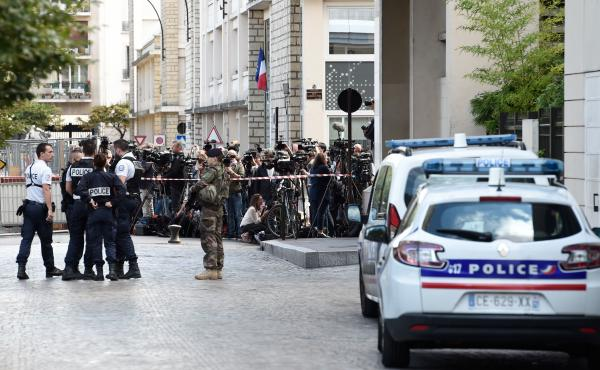 Journalists gather behind a cordon as police work at the site where a car slammed into soldiers in Levallois-Perret, a Paris suburb, on Wednesday.