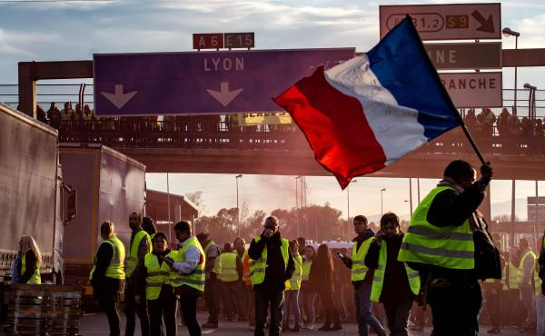 """A """"Yellow Vest"""" protester waves a French flag in Villefranche-sur-Saone on Saturday, during a demonstration against high fuel prices."""