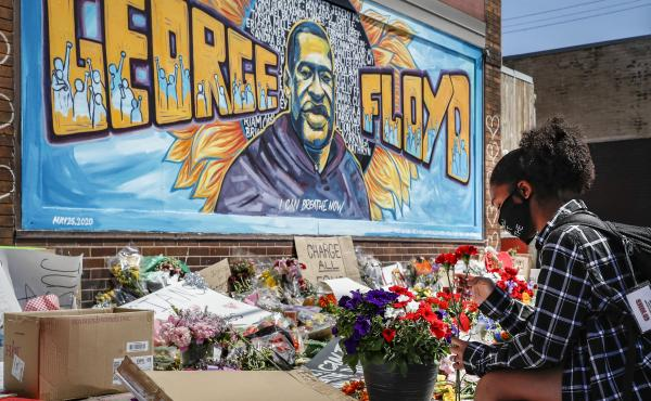 Malaysia Hammond places flowers at a memorial mural for George Floyd in Minneapolis on Sunday. Police brutality has sparked days of civil unrest. But the sparks have landed in a tinderbox built over decades of economic inequality, now exacerbated by the c