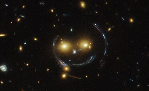 An image taken with the NASA/ESA Hubble Space Telescope of the galaxy cluster SDSS J1038+4849 shows that it seems to be smiling. The space agency says it's the result of a symmetrical alignment of the galaxy cluster and the telescope — along with a powe