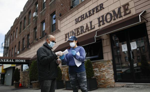 Employee Gina Hansen (right), hands documentation to a client outside Daniel J. Schaefer Funeral Home in Brooklyn, on April 2, 2020.