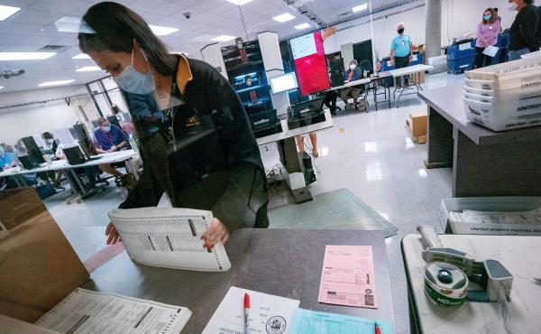 A poll worker sorts ballots inside the Maricopa County Election Department in Phoenix on Nov. 5, 2020. Republican voting bills in Arizona are on hold after a GOP state senator came out in opposition.