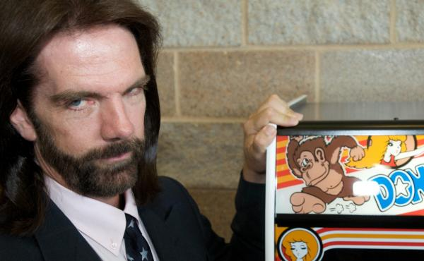 """Billy Mitchell, described once as """"Video Game Player of the Century,"""" poses for a portrait in front of Donkey Kong in Ottumwa, Iowa, in 2009."""