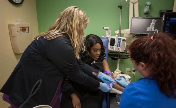 As part of a clinical trial to treat sickle cell disease, Victoria Gray (center) has vials of blood drawn by nurses Bonnie Carroll (left) and Kayla Jordan at TriStar Centennial Medical Center in Nashville, Tenn.