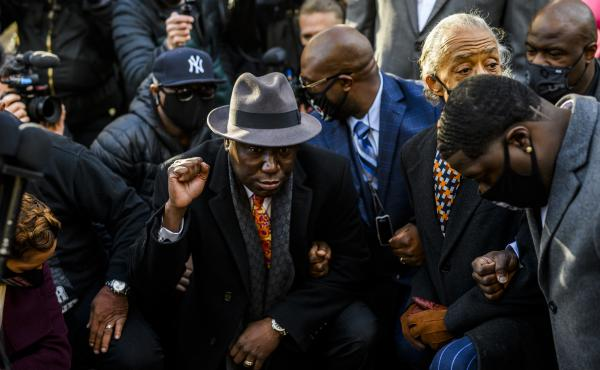 Attorney Ben Crump (center) took a knee with members of George Floyd's family and Rev. Al Sharpton for 8 minutes and 46 seconds outside the Hennepin County Government Center in Minneapolis, Minn., on Monday, shortly before opening arguments began in the t