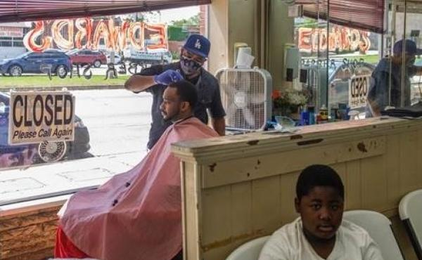 Marian Searcy cuts Shaquille Sanders' hair at Edward's Barber Shop in Macon, Ga., on Friday, the first day Gov. Brian Kemp said some businesses could reopen.