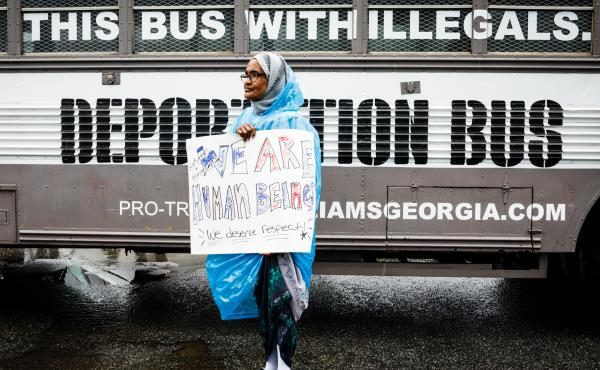 "Amina Osman protests Georgia state Sen. Michael Williams's ""Deportation Bus"" that reads ""Fill this bus with illegals."" She has been a resident of Clarkston, Ga. for nine years and is a refugee from Somalia."