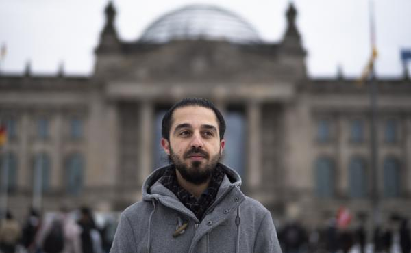 Tareq Alaows stands in front of the Bundestag, Germany's parliament, in Berlin. Alaows came to Germany as an asylum-seeker from Syria in 2015. He launched a campaign to run in Germany's federal election in September for the Green Party but recently withdr
