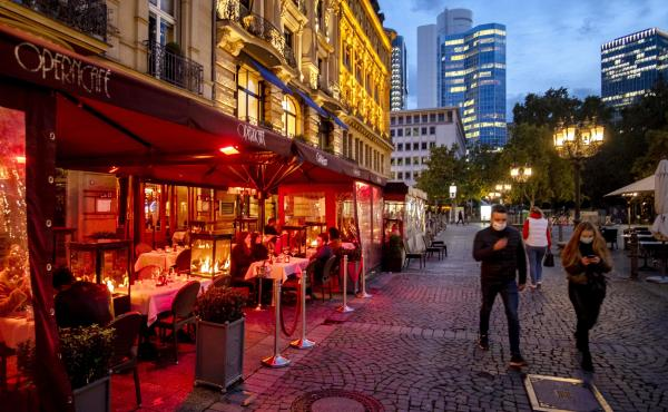 People wearing face masks walk past an outdoor restaurant Wednesday in Frankfurt, Germany. To slow the spread of the coronavirus, restaurants will be closed, starting Monday.