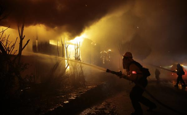 Firefighters try to battle the flames ravaging homes Monday in Los Angeles, as the Getty Fire threatens lives and structures around the city.