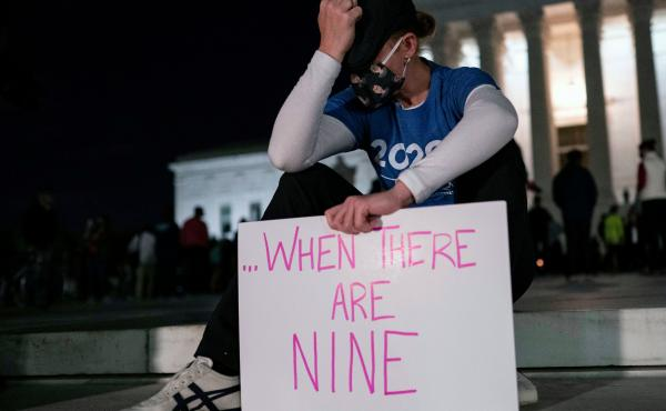 "A woman, mourning the death of Ruth Bader Ginsburg, holds a sign at the Supreme Court that reads, ""when there are nine,"" something Ginsburg said to describe when there'd be enough women on the court."