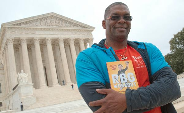 "Bryant Johnson, who was Justice Ruth Bader Ginsburg's personal trainer, poses at the court in 2017 with his book, ""The RBG Workout: How She Stays Strong ... and You Can Too!"""