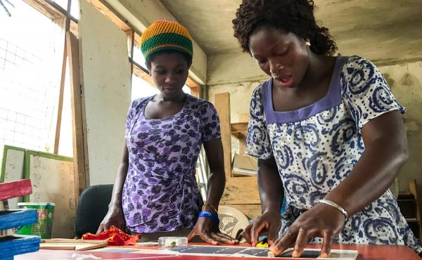 """Judith Ausah (left) and Evelyn Sewodey create solar panels at the Lady Volta Vocational Center for Electricity and Solar Power in Ghana. """"At first, I thought it was man's work,"""" says Ausah, whose 2-month-old daughter stays in the school nursery. """"But I ca"""