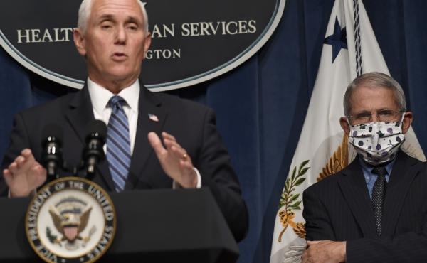 Dr. Anthony Fauci, right, director of the National Institute of Allergy and Infectious Diseases, listens as Vice President Pence speaks during a news conference Friday at the Department of Health and Human Services. The U.S. has lost more people to COVID-