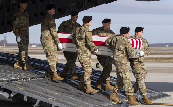 In this Dec. 25 photo, an Army carry team moves a transfer case containing the remains of U.S. Army Sgt. 1st Class Michael Goble, at Dover Air Force Base in Delaware. The U.S. Special Forces soldier died in Afghanistan this week while seizing a Taliban we