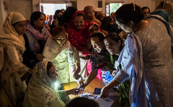 Pakistani women jostle to receive their ballot papers prior to casting their ballot at a polling station on May 11, 2013 in Lahore. A study in The Lancet provides evidence that free and fair elections are associated with a lower burden of chronic diseases