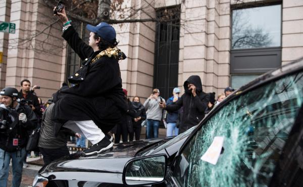 A man takes a selfie on the hood of a destroyed limousine during an Inauguration Day protest against President Trump on Jan. 20 in Washington, D.C. The Department of Justice has been cleared to search through website records related to organizing protests