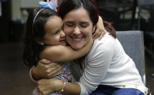 Natalia Oliveira da Silva and her daughter, Sara, 5, hug at a Catholic Charities facility in San Antonio, TX. They were separated in late May.