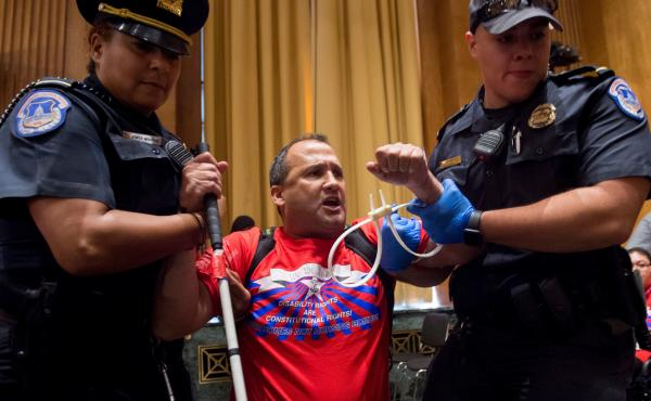 U.S. Capitol Police remove a protester from Monday's Senate Finance Committee hearing on the Graham-Cassidy health care plan to repeal Obamacare.
