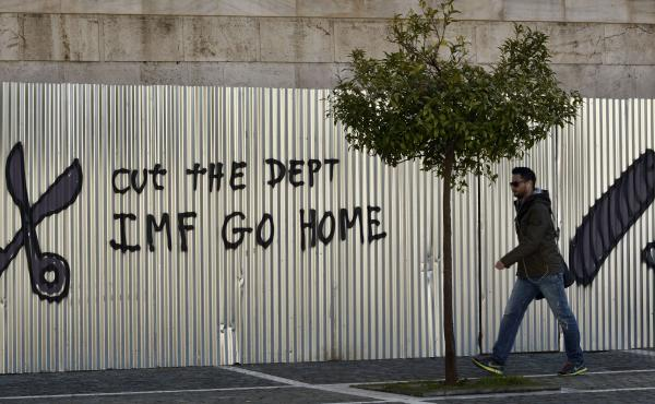 A man passes a graffiti in central Athens Friday, as Eurozone finance ministers consider Greece's request to extend the bailout loans that have kept its government afloat.