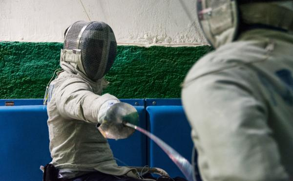 Panos Triantafyllou (left), in his fencing uniform and mask, trains with Vasilis Ntounis, his fellow Paralympic athlete and close friend.