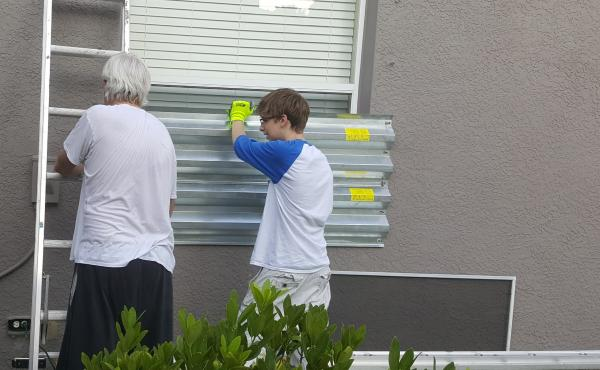 Greg Gatscher, left, and his son, Evan, prepare the house for Hurricane Irma. Little did they know these metal shutters would later become a cooktop.