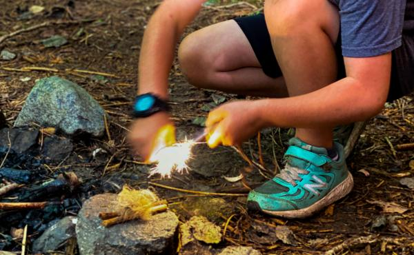Asher Wool, 8, uses a ferro rod and striker to light a bundle of tinder aflame at Earthwork school in western Massachusetts.