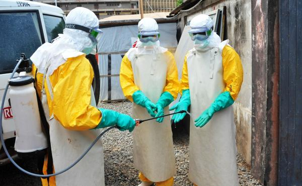 In a photo from Guinea's previous Ebola outbreak, medical staff clean their protection suits in March 2015 in Conakry, Guinea. Guinean authorities declared a new Ebola outbreak Sunday.