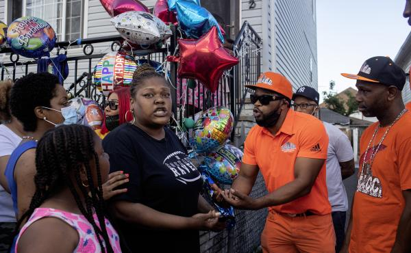 Shanduke McPhatter, a non-violence activist, talks to a woman who recently lost a relative to gun violence. The peace vigil took place on the block where 10-year-old Justin Wallace was shot to death.