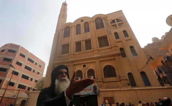 A priest reacts at the site of an attack on a church in Helwan, south of Cairo, on Friday. Officials say the attack killed at least nine people.