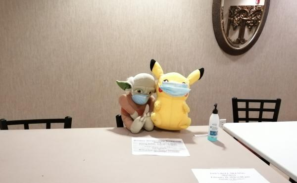 A masked Yoda and Pikachu guard a table with signs notifying evacuees of times for daily temperature checks.