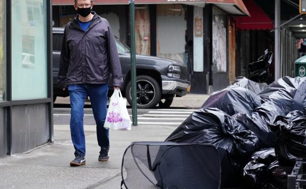 A man wearing a protective mask looks at piled-up trash in New York City on April 24. Cities are struggling with collection as the volume of residential garbage surges during the stay-at-home era.