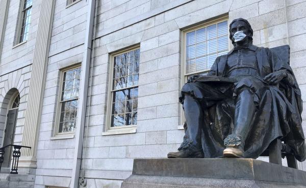 A statue of John Harvard, namesake of Harvard University, wears a face mask last month on the school's campus in Cambridge, Mass.