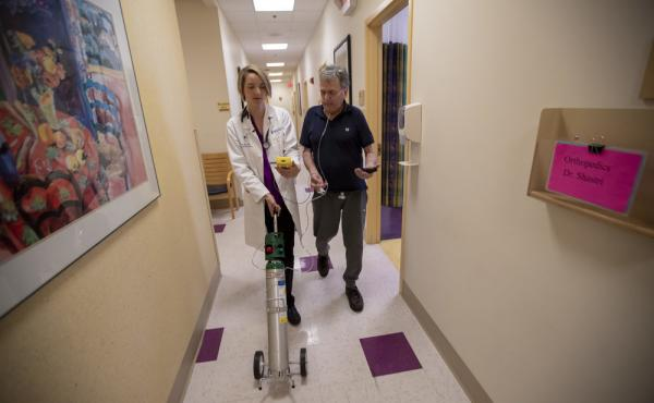 Dr. Mary Rice walks with Michael Howard at a Beth Israel Deaconess HealthCare clinic in Chealsea, Mass, as they test his oxygen levels with the addition of oxygen from a portable tank. He has COPD, a progressive lung disease that can be exacerbated by hea