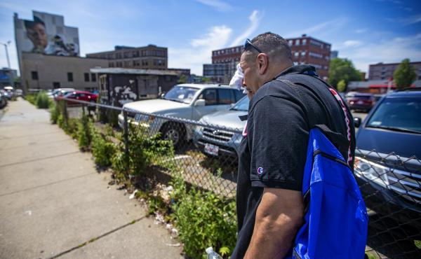 Will wipes away sweat on a hot day while walking down Willow Street in Lynn, Mass., as he looks to distribute safety supplies to drug users on the street.