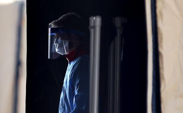 A health care worker prepares to screen people for the coronavirus at a testing site in Landover, Md., in March.