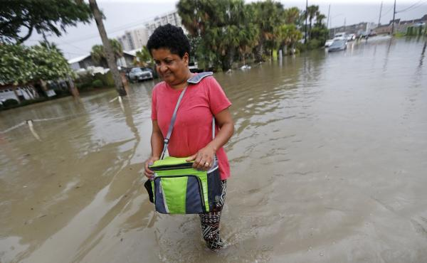 Esther Martens walk through a flooded roadway to get to her car in the West End section of New Orleans on Wednesday.