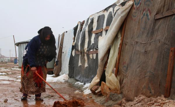A Syrian refugee shovels mud in front of a makeshift shelter in an unofficial camp for Syrian refugees in Iaat in Lebanon's Bekaa Valley on Tuesday.